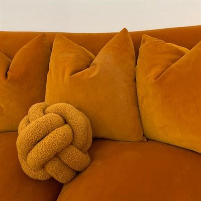 Mustard Boucle Knot Cushion on mustard sofa