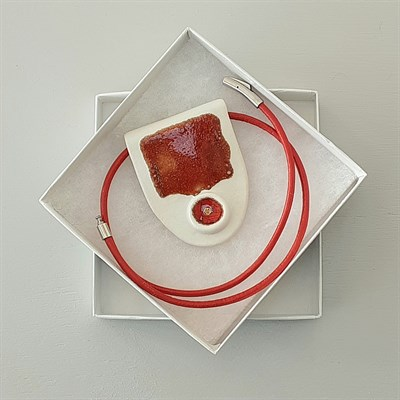 Porcelain necklace with red artwork in its box