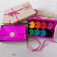 Open box of unicorn crayons with gift wrapped boxes surrounding.
