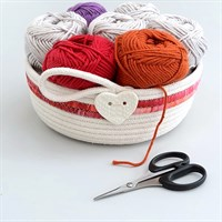 Cotton rope bowl with pink fabric trim full of balls of wool