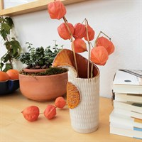Harlequin ceramic vase with orange glaze in room setting