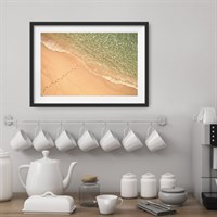 Photo art print 'Footsteps in the Sand' shown framed in a room setting