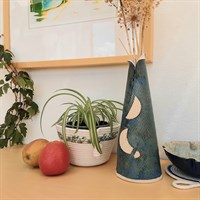 Tall conical blue ceramic vase in room setting
